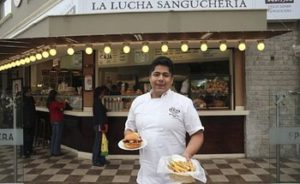 Restaurants In Miraflores - La Lucha staff member showing plates with dishes