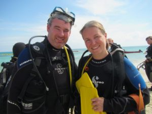 Sarah and Nathan from https://exploringkiwis.com posing after scuba diving