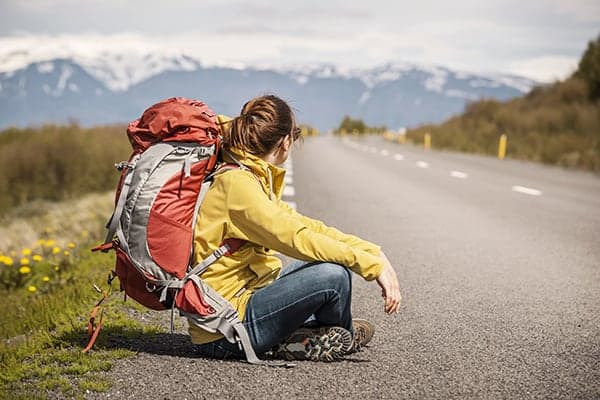 backpacker waits at the side of the road